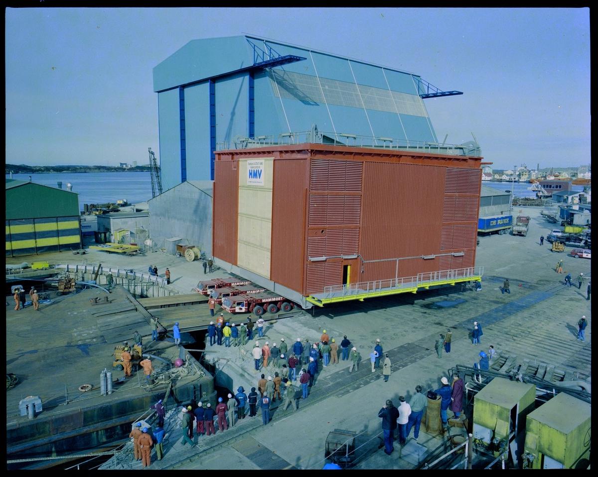 En stor modul til Statfjord A fraktes mot en lekter på Haugesund Mekaniske Verksted. Flere har kommet for å se på, og i bakgrunnen står Nordsjøhallen.