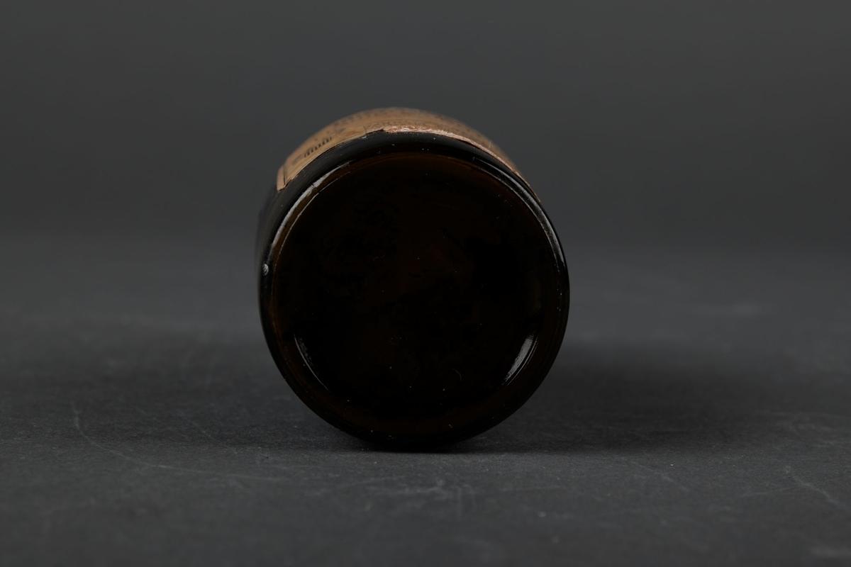 Et lite brunt glass-flaske med maling, med en trekork.