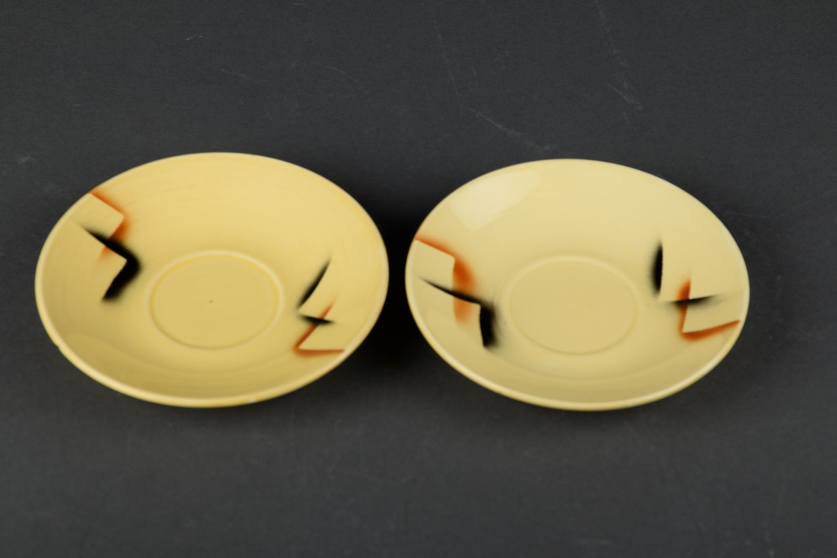 To gule tefat med brun og svart dekor.