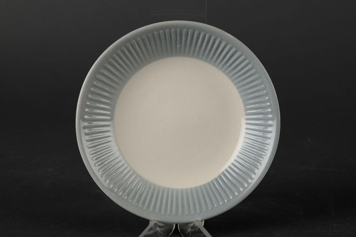 Hvitt tefat med blå-grå bølgete kanter.