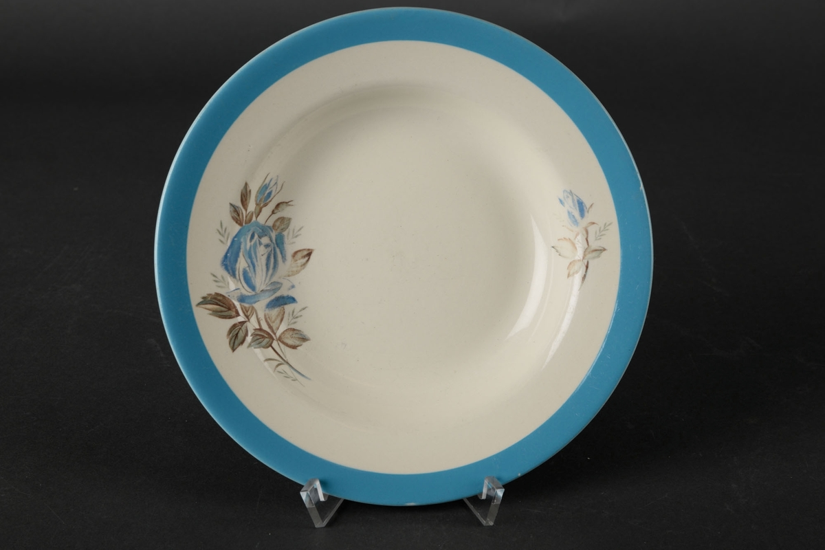 Hvit skål dekorert med en blå sirkel langs kanten, og to blomster, en stor og en liten, på hver side av midten.