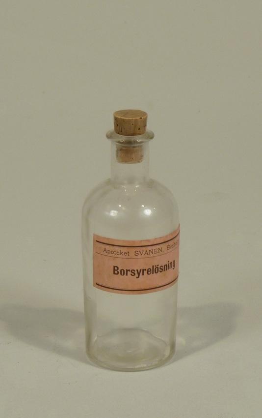 Medicinflaska med kork. Klart glas, rund bas. Rosa etikett med texten: Borsyrelösning.