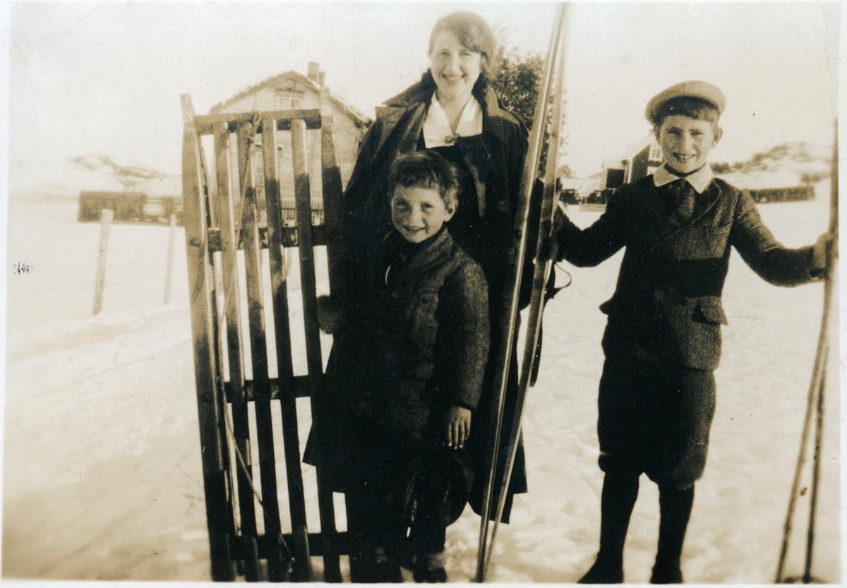 To gutter og en ung kvinne med kjelke og ski.