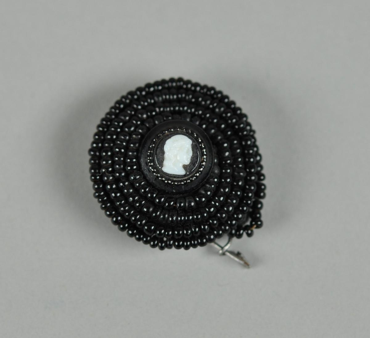 Brun brosje, sannsynligvis av bakelitt. En tråd av svarte perler er spiralisert rundt et hvit dame i profil, av bein.