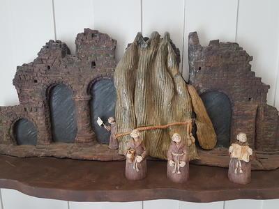 Fire munker i keramikk står og ser opp foran en kermaikkmodell av søylerekka fra domkirkeruinen på Hamar