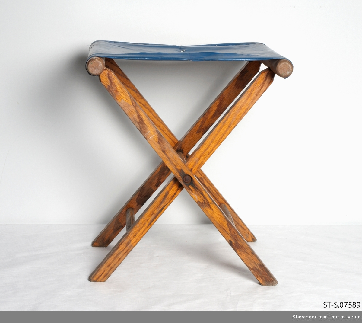 Klappstol i tre med blått plast sete, har også DSD logo på setet.