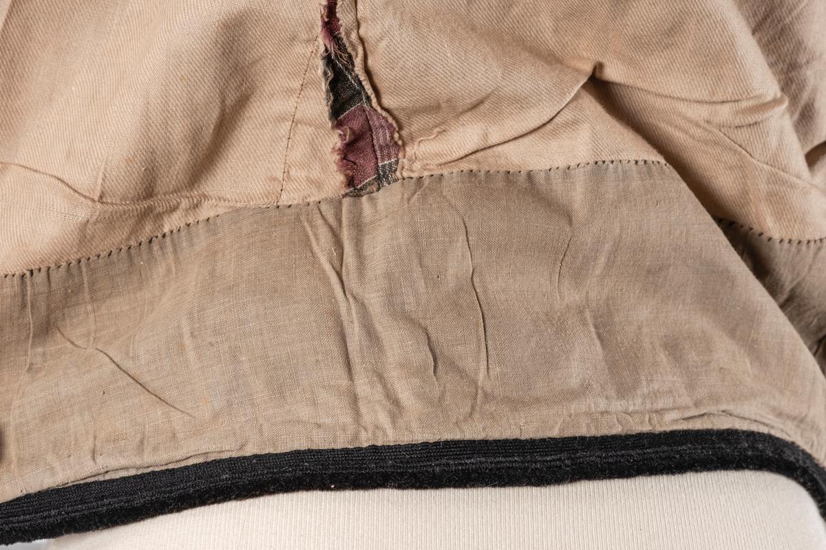 Ull- og bomullsskjørt med åpning bak. Rynka stoff bak i åpning og festing med metallhemper. Svart kant påsydd nederst. Lomme i høyre siden.