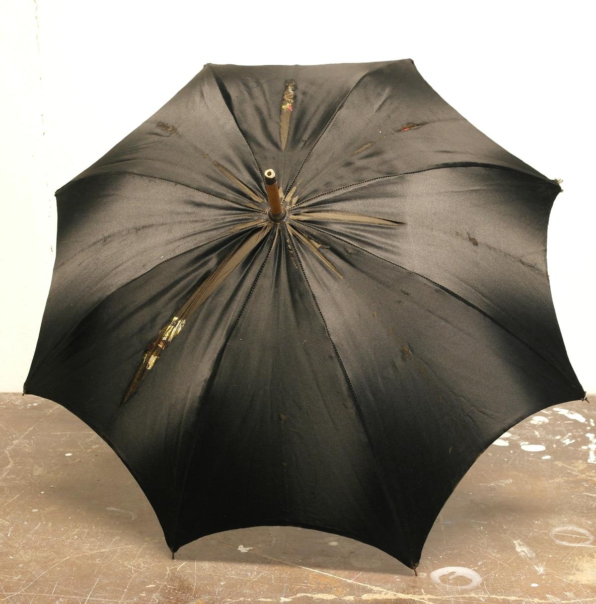 Parasoll laget av silke, messing og tre. Over messingspilene er det trukket et dobbeltsydd silkestoff som er sydd fast ytterst på hver spile. Stoffet har blomsterbroderi på innsiden, som kommer frem når parasollen er oppslått. Parasollen har et langt, smalt treskaft og buet håndtak med snor og pomponger.