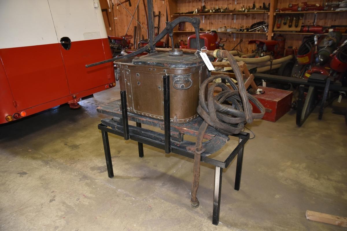 Brannpunpe med vannkar/tank av kobber med fire håndtak på sidene. Karet har rektangulær form med avrundede hjørner. Et lokk dekker 2/3 av åpningen. Tohånds pume er festet på lokket. og har stempel som heves og senkes med pumpearmens posisjon. Pumpen har tilhørende lærslange med strålerør med kupling. Slangen festes til pumpens høyre side ved bruk. Pumpen er montert på en sluffe/slede.