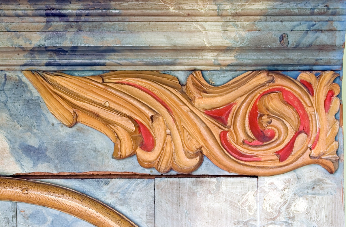 Skåp av furu. Bred profilerad rak krönlist. Två dörrar, med låset placerat på vänster dörrhalva. Framsidan är rikt dekorerad med bland annat utskurna och målade dekorelement av trä målade i gulbrunt och rött. På dörrarna listverk målade i gulbrunt. På förhöjningar utanför listverket pålagda dekorelement i form av eldslågor målade i rött. På dörrspeglarna pålagda dekorelement med utgående strålar målade i gulbrunt och rött, omgivna av målade korslagda kvistar. I övrigt är skåpet marmorerat i blå och vita toner. Nedre delen av skåpet målat i rosa och gulbrunt och partiet mellan frambenen svängt. Invändigt tre hyllor, varav en skedhylla. På den mellersta hyllan hänger en draglåda.  Invändigt omålat liksom höger utsida, då skåpet är tänkt att placeras i ett hörn.