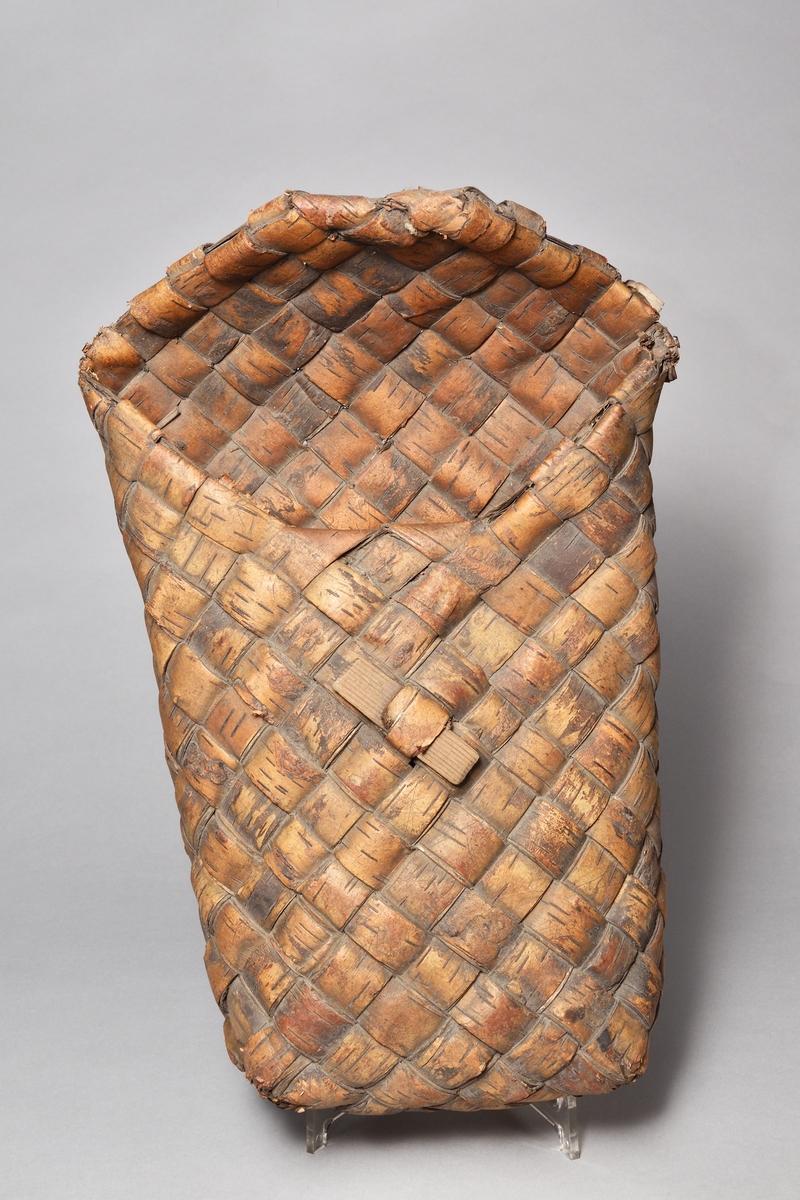 Kont, vallkont, av flätad näver med lock, stående rektangulär. En furusticka på fronten att stänga locket med.