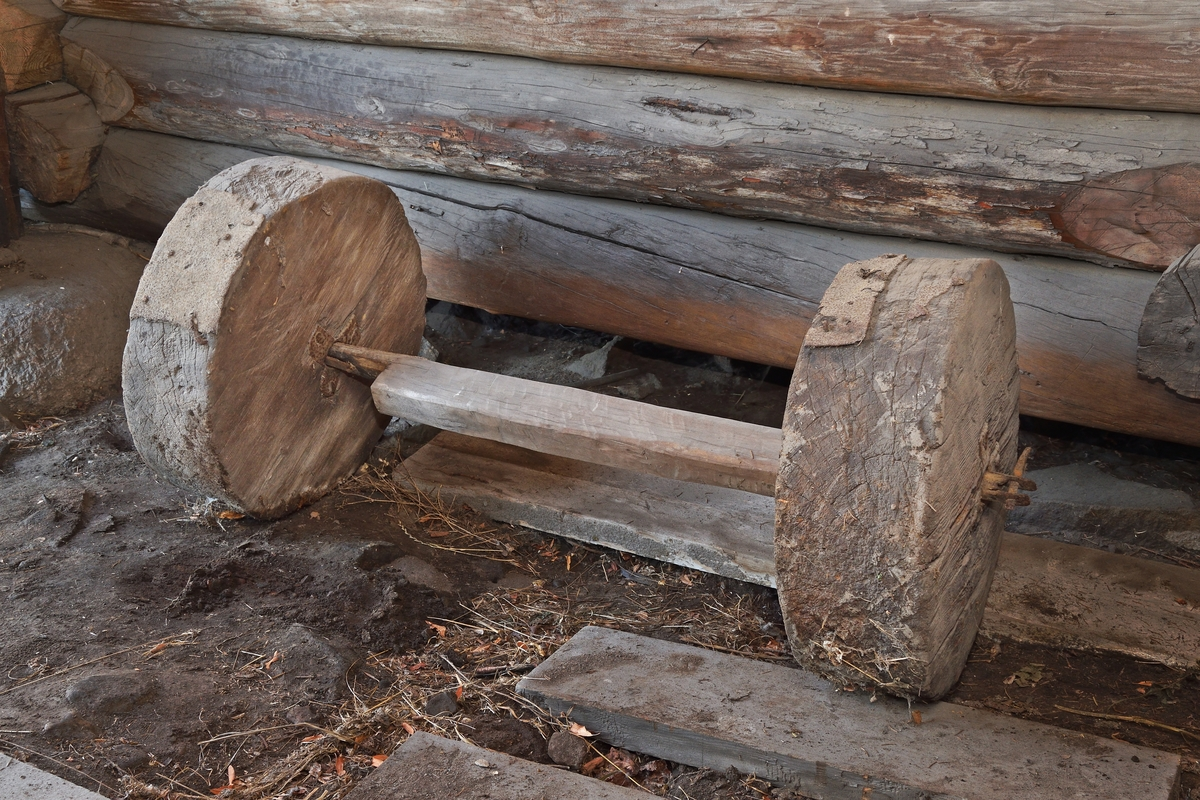 Hjul, 2 st av massivt trä, centrumhålen järnfodrade. Axel av trä med järnbeslag i båda ändar.