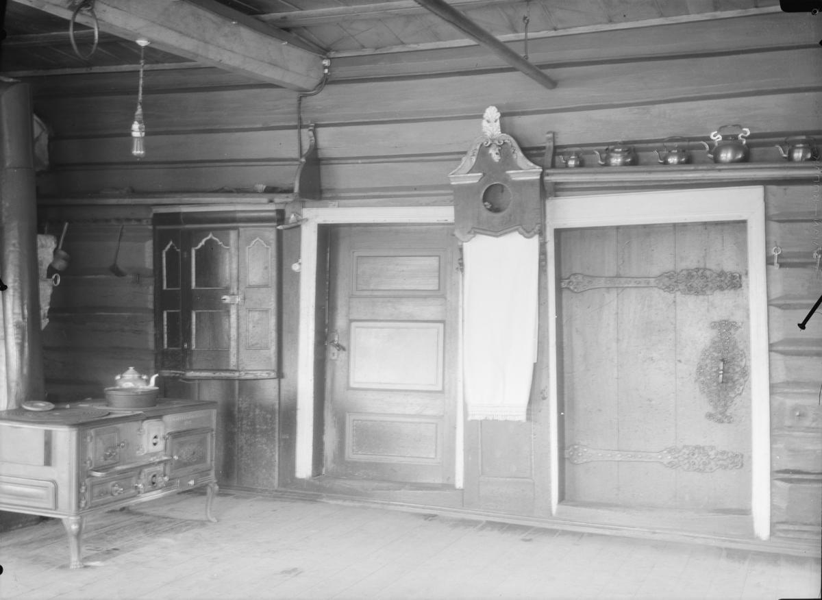 Interiør, kjøkken med tømmervegger, to utgangsdører med bostkast i mellom. Over ene døra står kaffekjeler. Innebygd skap til venstre med jernovn