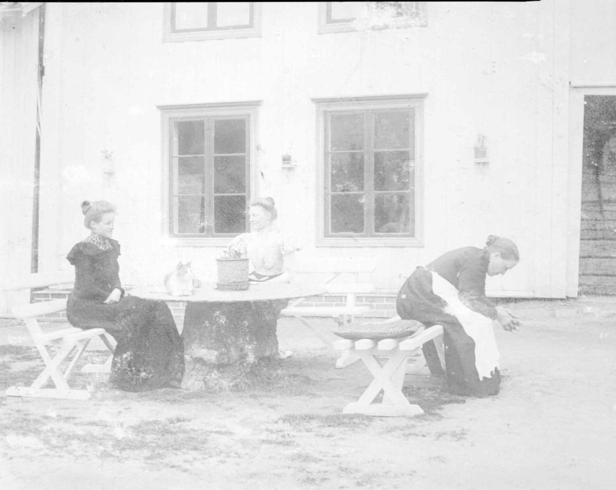 Repro: Tre kvinner sittende på gårdsplass på Vingnes.
