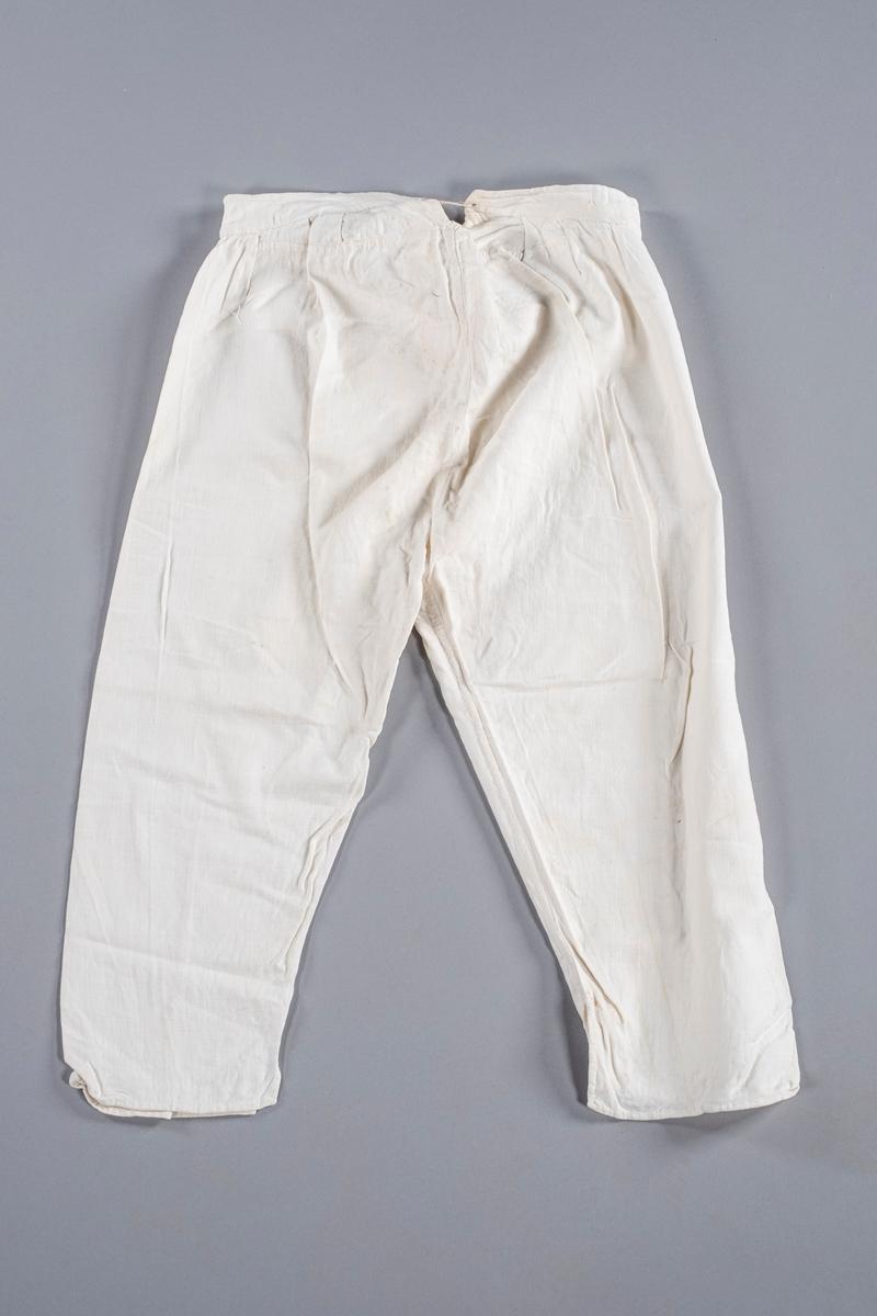 Underbukse i hvit bomull med åpning i front med to knapper, og åpning bak med snøring. Den har folder ved linningen. Nederst i beina er det splitt.