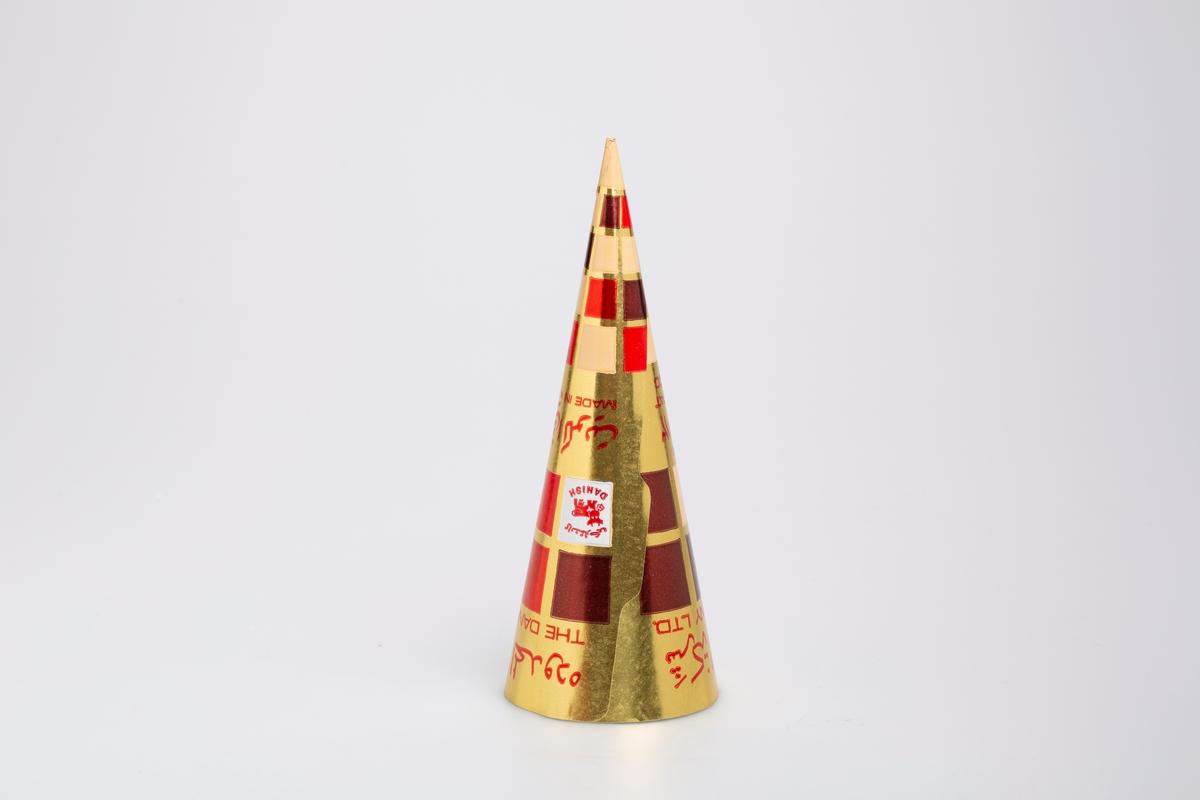 Kjegleformet iskrempapir (kremmerhus) i aluminium og papir. Kremmerhuset er med farger på utsiden, og uten farge (hvit) på innsiden. Iskrempapiret har gullfarget bakgrunn med ruter i brun, rød og beige. Deler av tekstene er i et annet skriftsspråk.
