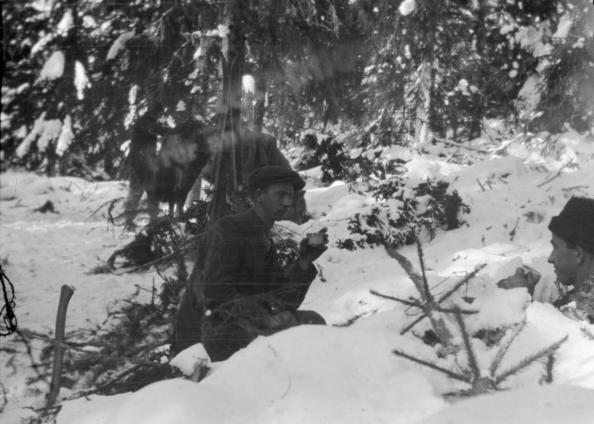 Vinterbilde med to menn som drikker kaffe i snøen.