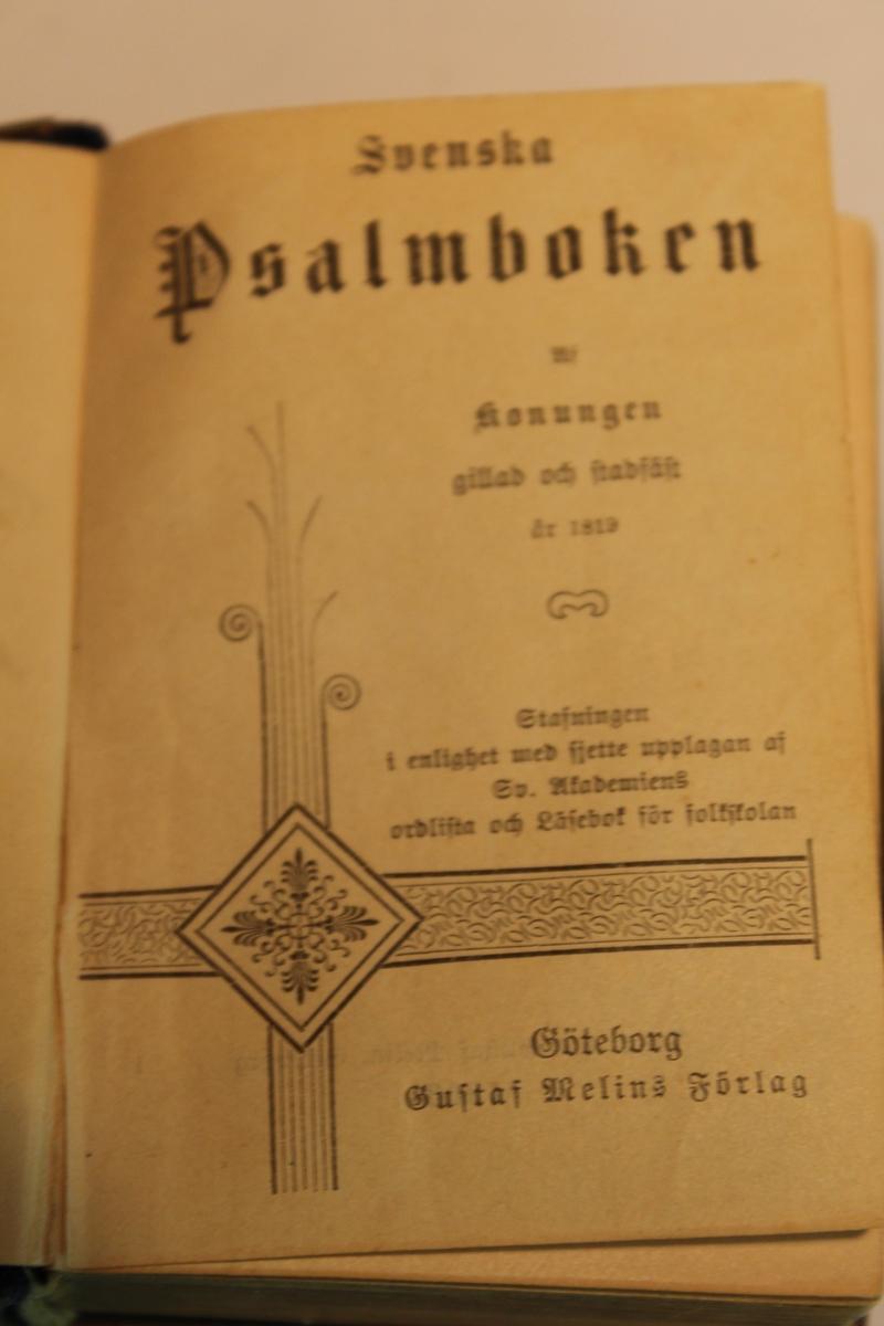 Liten psalmbok tryckt 1903. Med pärmar i svart sammet och ett dekorerat kors i mässing på framsidan samt ett spänne på ena sidan. Pärmarna är även kantade med mässing.