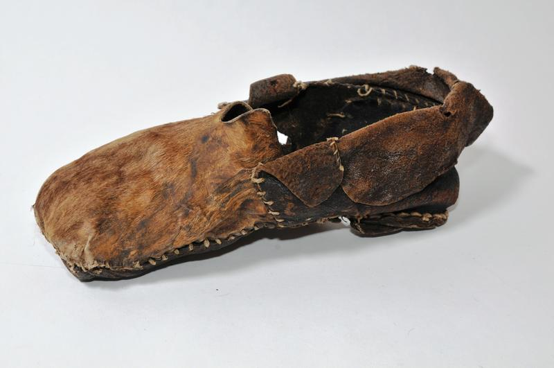 Desse to skoa er funne i Ulnes. Begge er laga av hud/skinn og har sålar av lær i eitt lag. Overdelen er av kuskinn med hår. Skoen til venstre har oppklipt kort splitt midt framme. Bakre delen er av glatt skinn og det er påsydd ein krage langs øvre kanten.  Skoen har skinnsnøring i eine sida. Skoen til høgre har overdel framme av kuskinn med hår, medan bakre delen er av grisehud med bust. Foto: NBF (Foto/Photo)