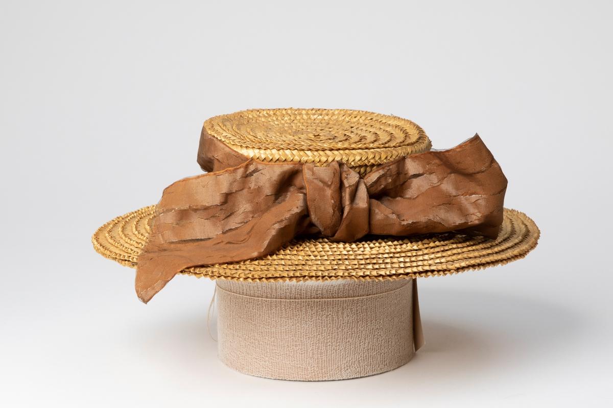 Maskinsydd halmhatt i rak modell. Kullens kant är utsmyckad med ett 10 cm brett brunt sidenband inklätt i brunt organza, bandet avslutas med en stor rosett på vänster sida. Insidan är klädd med ett ljust, glest, något hårt tyg som skydd mot hattens hårda flätning.