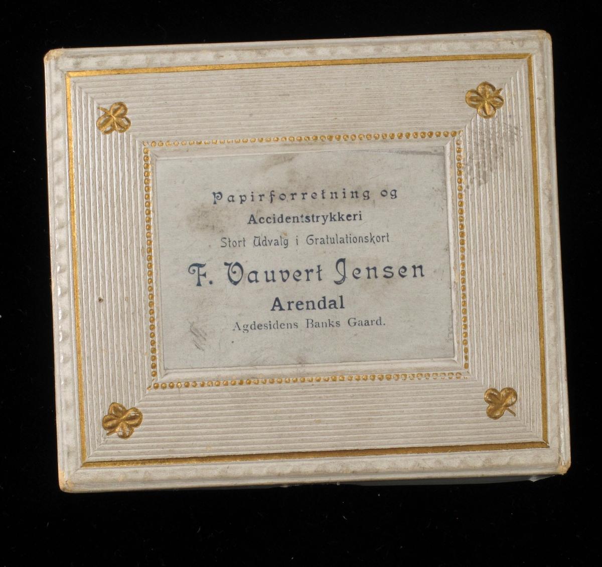 Vareeske av kartong, dekorert med påtrykt mønster og firmanavn. Eskelokket er dekorert med preget mønster, linjer, perler og firkløver.