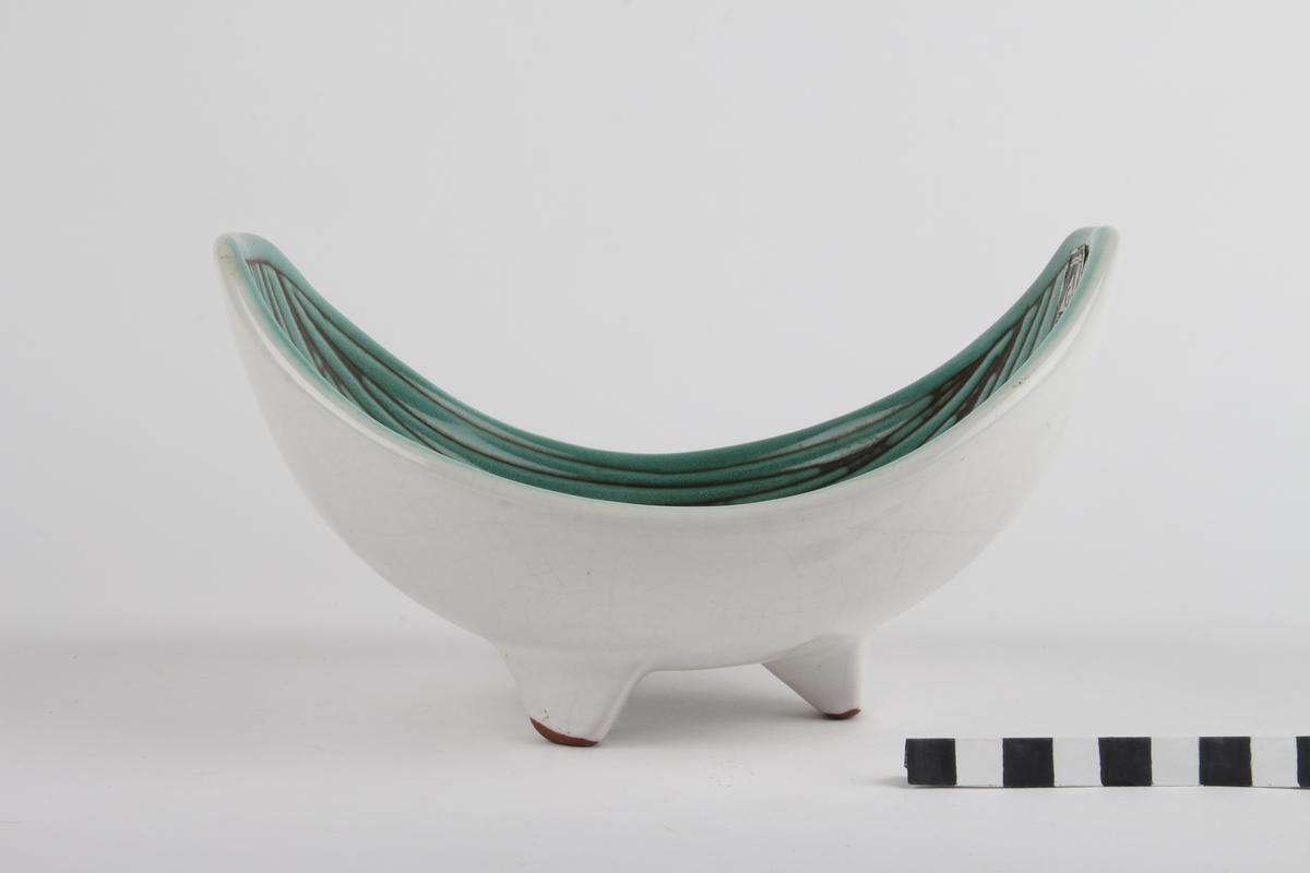Båtformet skål med dekor og tre ben.