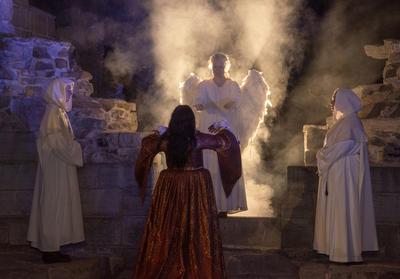 En engel stiger fram fra lys og røyk for å hente den døde Jomfru Karine.