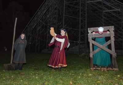 Bøddelen står til venstre, midt i bildet er en dommer i ferd med å lese opp urettene og straffen til ei av konene i kaupangen. Hun står i gapestokken. (Foto/Photo)