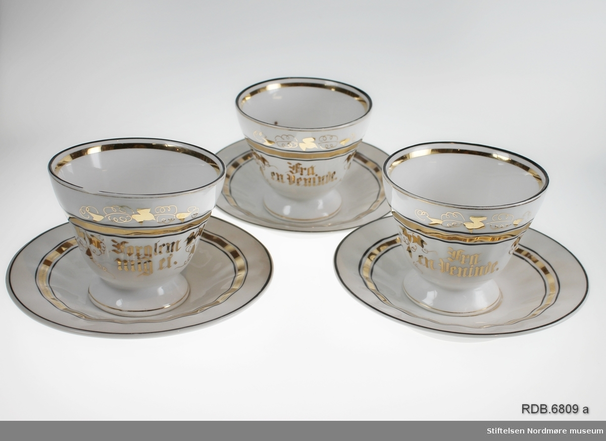 """Tre hvite kopper med lav stett og tilhørende skåler. Både kopper og skåler er dekorert med gull- og svarte striper. To av koppene har påskift: """"Til en veninde"""", og den tredje: """"Forglem mig ei"""" skrevet med gotiske bokstaver. Den siste koppen har et skår på kanten. Blått fabrikkstempel under."""
