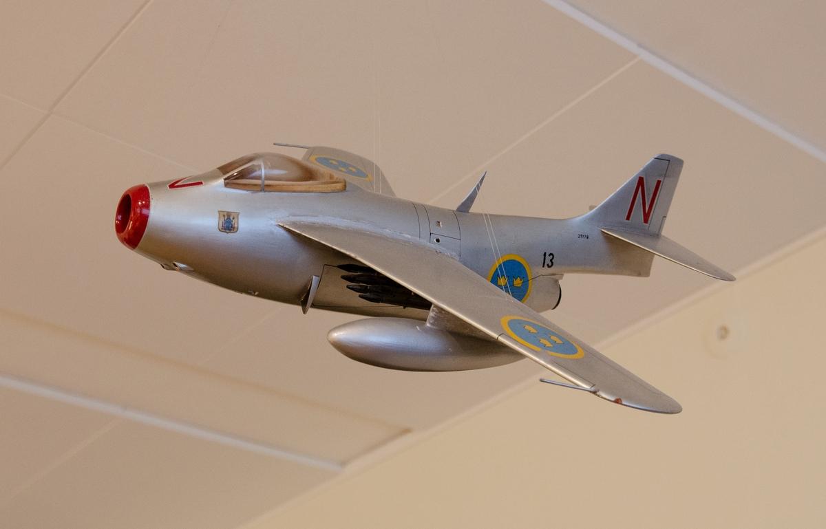 Flygplansmodell av trä i skala 1:20. Massivt trä. Modellen är målad enligt Målningsritning för flygplanstypen och märkt med divisionsbeteckning röd N samt F 13. Modellen är byggd av Rune Johansson (Termik Johan) Norrköping.