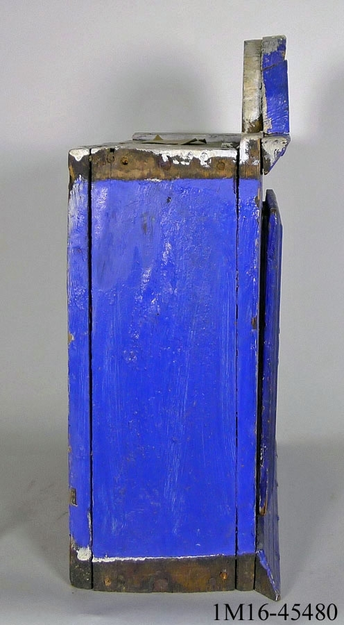 Väggskåp, häng, i furu. Stommen ihopsatt med träplugg. Fronten ihopsatt med fast tapp/tapphål, låst med träplugg. Fronten sitter fast på stommen med träplugg. Upptill svängt krön. Nedtill profilerad list, sidlisterna saknas. Massiv dörr - avhäcktningsbar från gångjärnen. Dörren har nyckelhålsbeslag men saknar låskista. Innuti, två i spår infällda hyllplan. Bakstycke fastsatt med träplugg och spik. Originalmålning - brun, nu målad med kraftig blå/vit färg.