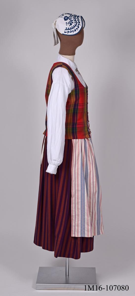 Komplett Vilskedräkt.  Vilskedräkten är en så kallad konstruerad folkdräkt. Den är sammansatt av olika delar som kommer från skilda delar inom Vilske kommun. Kommunen finns inte längre kvar. Modellen för väskan bars av Anna Charlotta Persson, Vrågården vid sitt bröllop 4 juli 1865. Förlagan till kjolen kommer från Ullene. Förlagan till förklädet kommer från Sörby. Förlagan till mössan är från 1830-1835 och kommer från Trevattna. Förlagan till halssmycket kommer från Gökhem. Förlagan till ytterschalen har tillhört Karl Edberg från Hällestad.