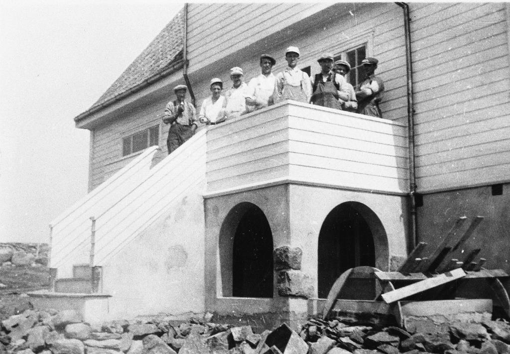 Prestebustaden på Time under bygging. Arbeidsfolk på verandaen.