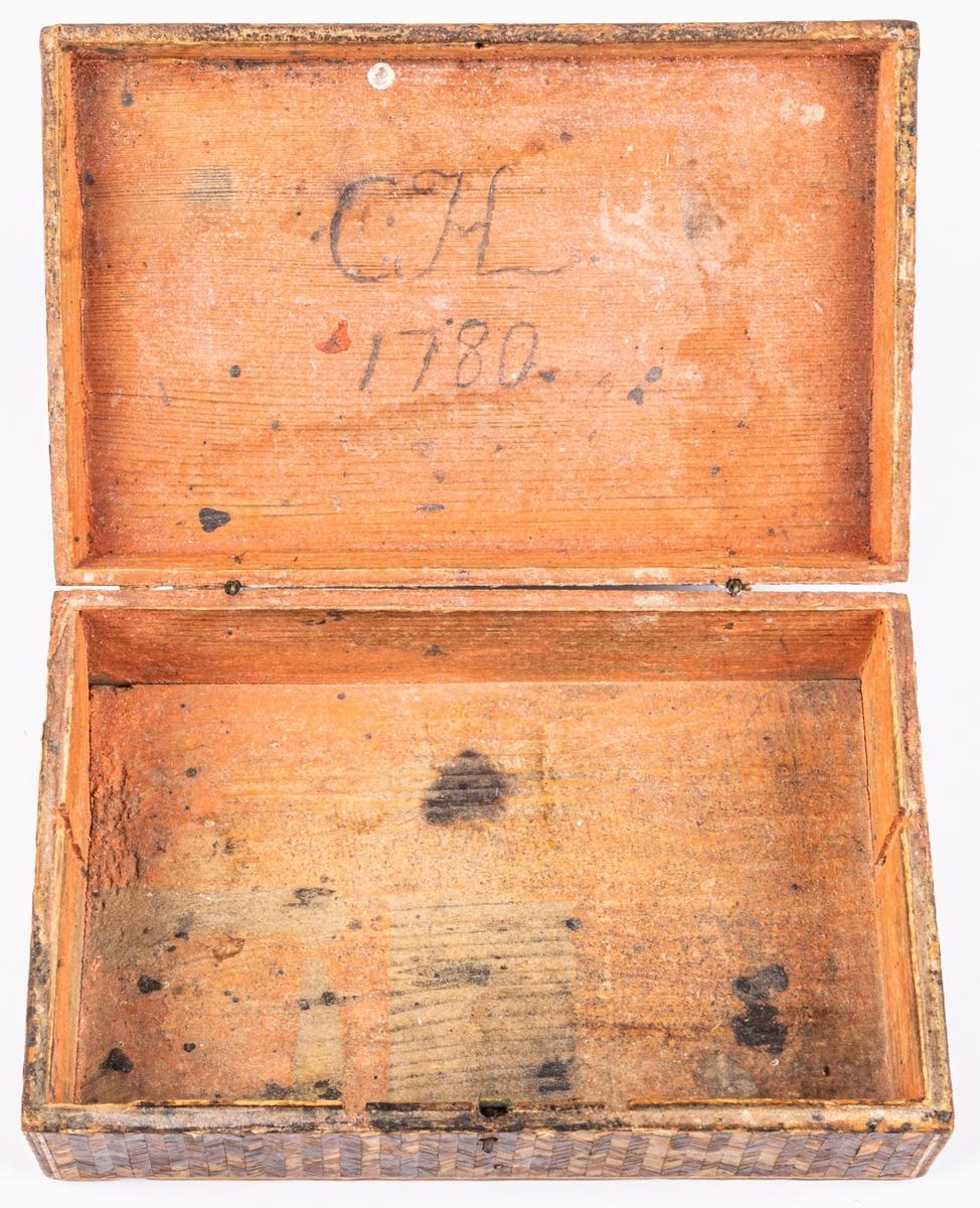 """Kat.kort: Skrin, av trä med halminläggningar /?/ eller fanér. Spår av fackindelning: för skrivsaker. Inuti skrivet """"C.H. 1780"""". Lock. I lockets utsida intarsia: C.I.H. med lejon, krona m.m. Har tillhört frkn Ebba Fick, Gävle."""