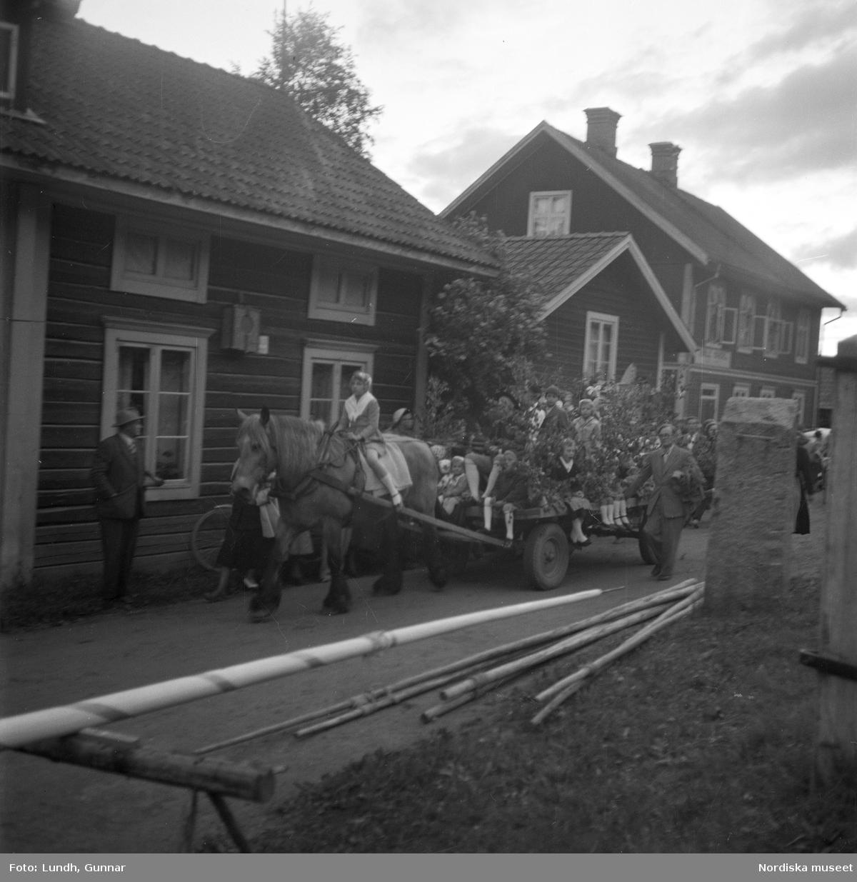 """Motiv: (ingen anteckning) ; En kvinna och två män spelar boccia, porträtt av en kvinna i folkdräkt, en folksamling står vid en gärsgård, tre män i folkdräkt rider på hästar framför män som spelar fiol och kvinnor i folkdräkt som går på en väg """"Midsommartåget till Tibble"""", en kvinna i folkdräkt rider på en häst som drar en vagn med barn, kvinnor och män pryder en midsommarstång med lövade ringar.dju"""