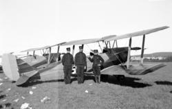 Militärt flygplan. Tre värnpliktiga i uniform m/ä.