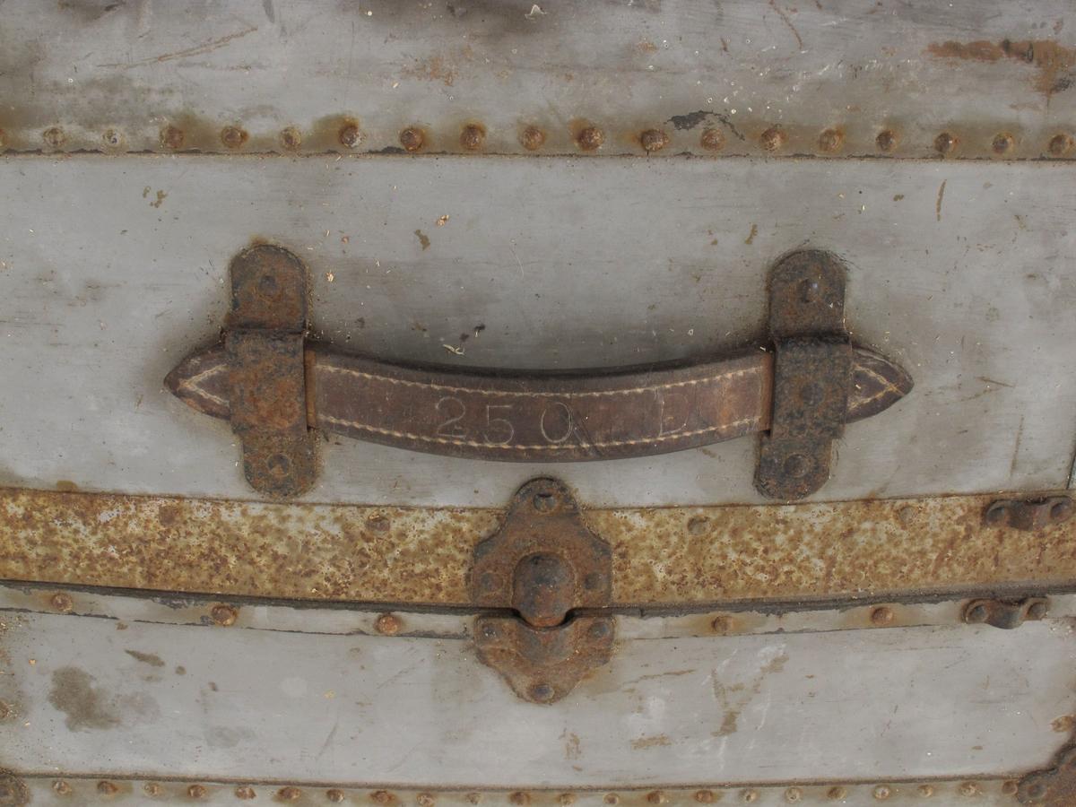 Stor solid koffert med beslag, låser og etiketter. Har vært med på reise med Den norske amerikalinje.
