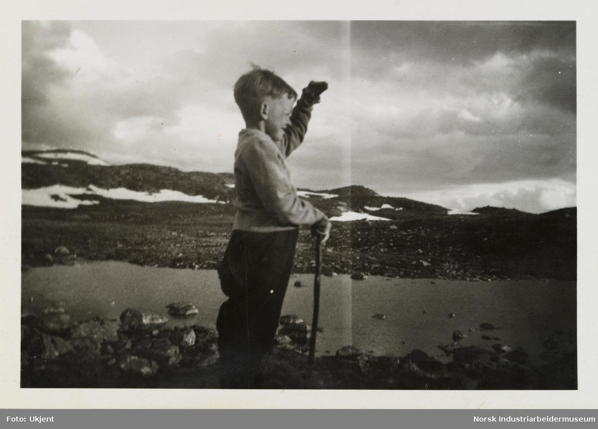 Olav O. Vågen står ved Olavsbu med pinne i hånden og skuer utover
