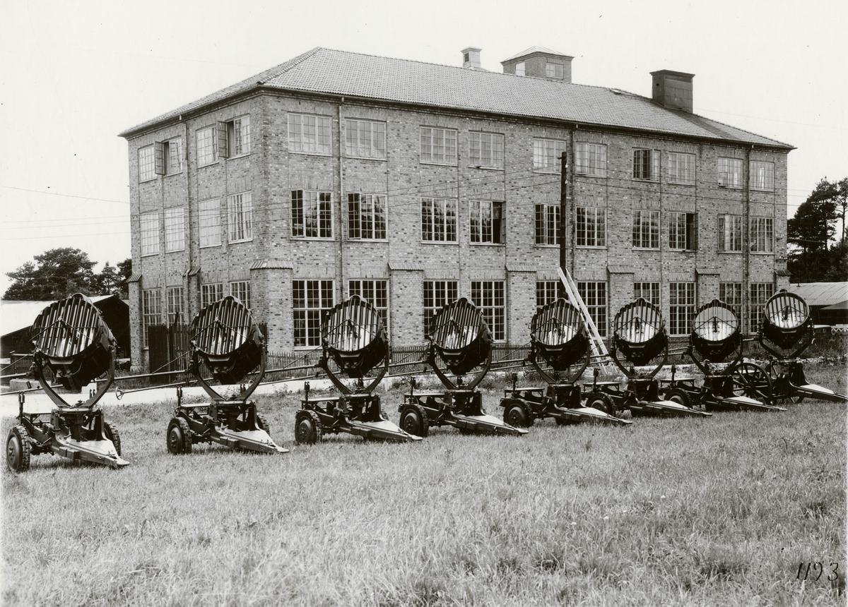 Strålkastare med 90 cm spegeldiameter, högeffektlampa och lavett med skivhjul, typ OH, lysläge. Tillverkad av Svenska Instrument Aktiebolaget (SIA).