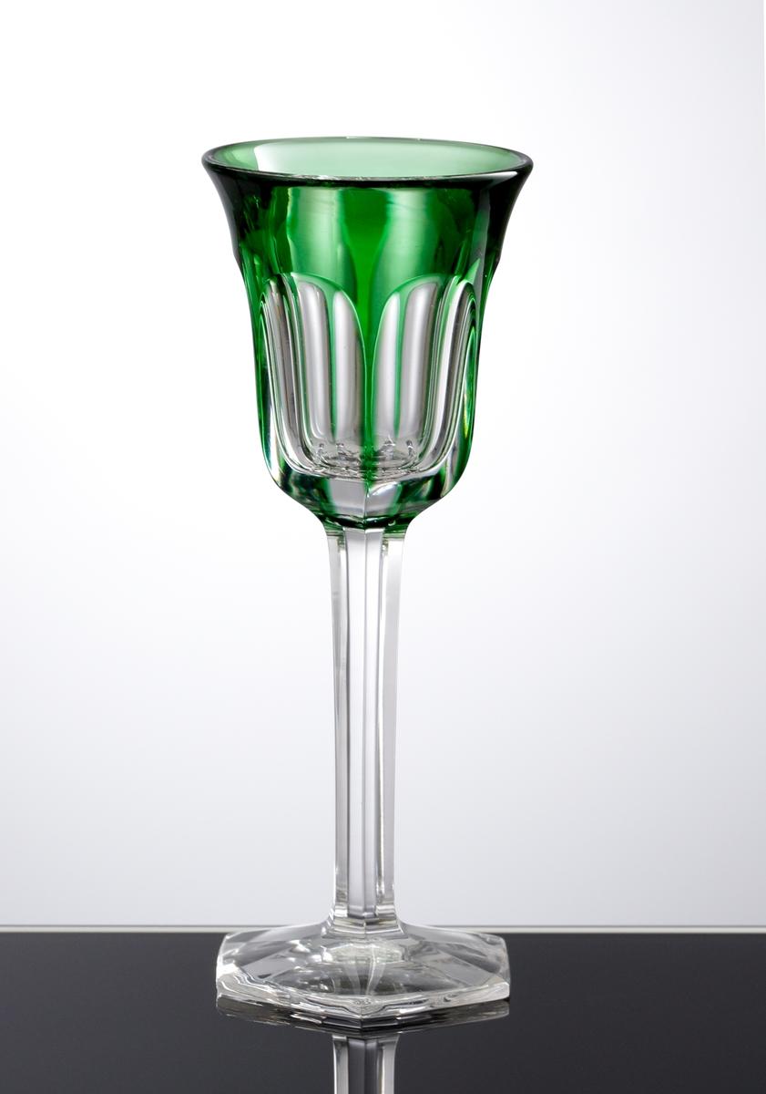 Likörglas med slipade facetter på kupan som har grönt överfång. Slipat ben och slipad sexkantig fot.