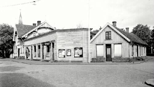 På skyltarna kan man läsa, Skomakeri A&E WASS, Cigarraffär S LIND, Järnvägshotell, Olympia, Storan och Folkparken.  Byggnaderna till vänster revs 1973, de till höger fanns 1938 men inte 1945.