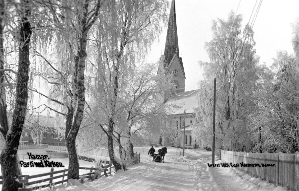 Svart-hvitt foto av rimete bjørketrær som leder ned mot Hamar Domkirke, og en hest med slede rett foran kirken.