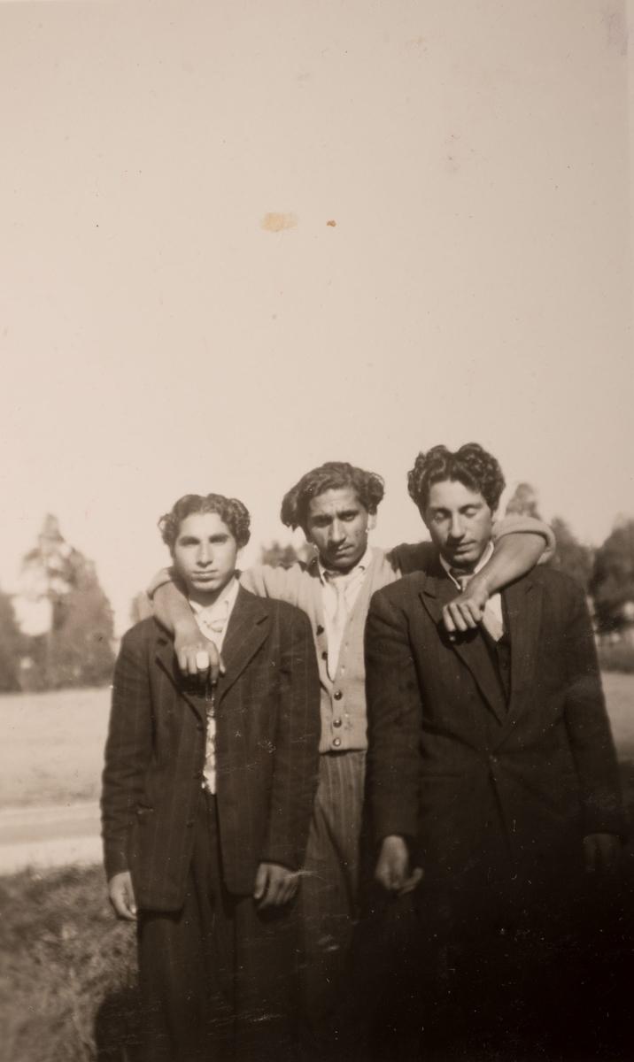Tre romska män i ett läger i Sandviken, juni 1947. Mannen i mitten har lagt armarna om de två männen som står på var sin sida om honom honom.