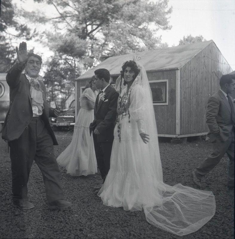 Nygift romskt par vid bröllop, november 1958 i Nyköping. Äldre romsk man välsignar paret. I bakgrunden syns uppställda vagnar, baracker och bilar i lägret. Svenska romer har historiskt tvingats bo i läger, ofta i samhällets utkant, då man har förvägrats fast bostad och fördrivits. Toleransen för romer har historiskt varierat mycket mellan olika samhällen, men romers närvaro har sällan setts som något positivt. Efter att de svenska romerna i Sverige erkändes som medborgare år 1952 uppstod debatt kring gruppens svåra levnadsförhållanden. En statlig utredning genomfördes under 1954-1956 där en av slutsatserna blev att fast bostad var nyckeln till att lyckas med skolgång och arbetsliv. Från och med mars 1960 hade möjlighet att rekvirera statsbidrag för kostnader i samband med romers bosättning, vilket förenklade möjligheten för svenska romer att få tillgång till permantenta bostäder samt i förlängningen studier och arbete.