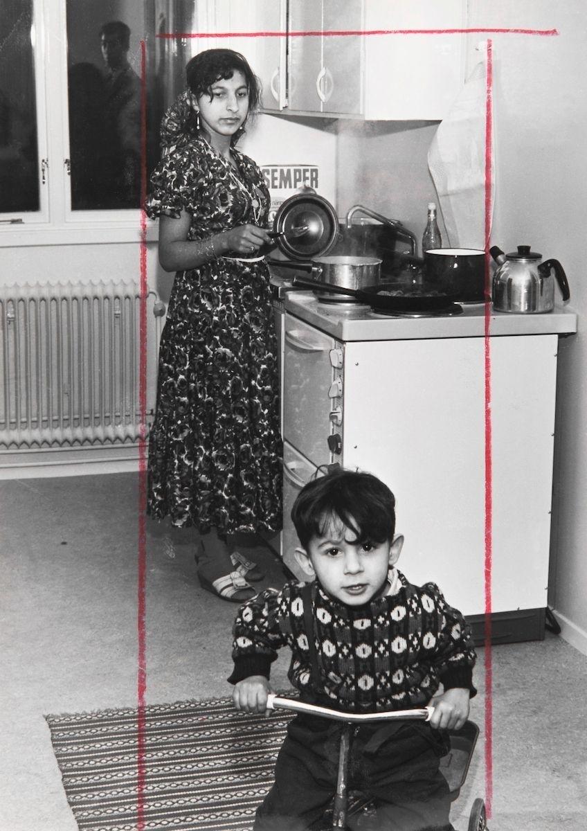 """Bilden föreställer en nyinflyttade kvinna och hennes son i köket i Uppsala, 1963. I texten som finns bevarad till bilden står det: """"Efter några års underhandlingar, gräl och kritik kan två familjer Taikon med tillsammans sex barn lämna iskalla husvagnar vid E4 strax utanför Uppsala och flytta in i nybyggda villor på """"industritomtområdet""""."""" Efter att de svenska romerna i Sverige erkändes som medborgare år 1952 uppstod debatt kring gruppens svåra levnadsförhållanden. En statlig utredning genomfördes under 1954-1956 där en av slutsatserna blev att fast bostad var nyckeln till att lyckas med skolgång och arbetsliv. Efter att även Stockholm stad genomfört en utredning (1955-57) upprättades två lägerplatser vid Flaten, samt en försöksverksamhet med provisoriska bostäder i Hammarbytäppan. Tanken var att romerna skulle bo här tills dess att bostadsfrågan löstes. De två lägerplatserna vid Skarpnäck låg med omkring 2 kilometers mellanrum. De kom att benämnas Ekstubben respektive Skarpnäckslägret. Skarpnäckslägret stod färdigt för inflytt i oktober 1959 och Ekstubben stod färdig för inflyttning 15 mars 1960. Lägren skulle finnas under en övergångsperiod innan fasta bostäder ordnats, men i realiteten drog bostadsfrågan ut på tiden och lägren blev kvar i fem år. Detta trots att kommuner från och med mars 1960 hade möjlighet att rekvirera statsbidrag för kostnader i samband med romers bosättning. Även denna process blev utdragen och det tog flera år innan fast bostad kunde erbjudas till alla svenska romer."""