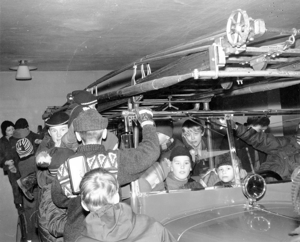 Brandkåren. Pojkar står vid och sitter i brandbil i Alingsås brandkårens garage på 1960-talet.