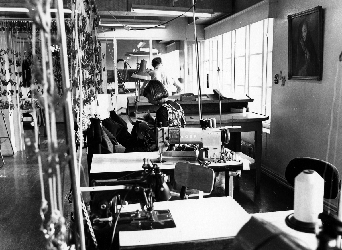 """Byxavdelningen, """"Byxan"""", Drabant AB:s tredje våning. Slutfasen av arbetet. En kvinna sitter vid ett bord och syr fickor."""