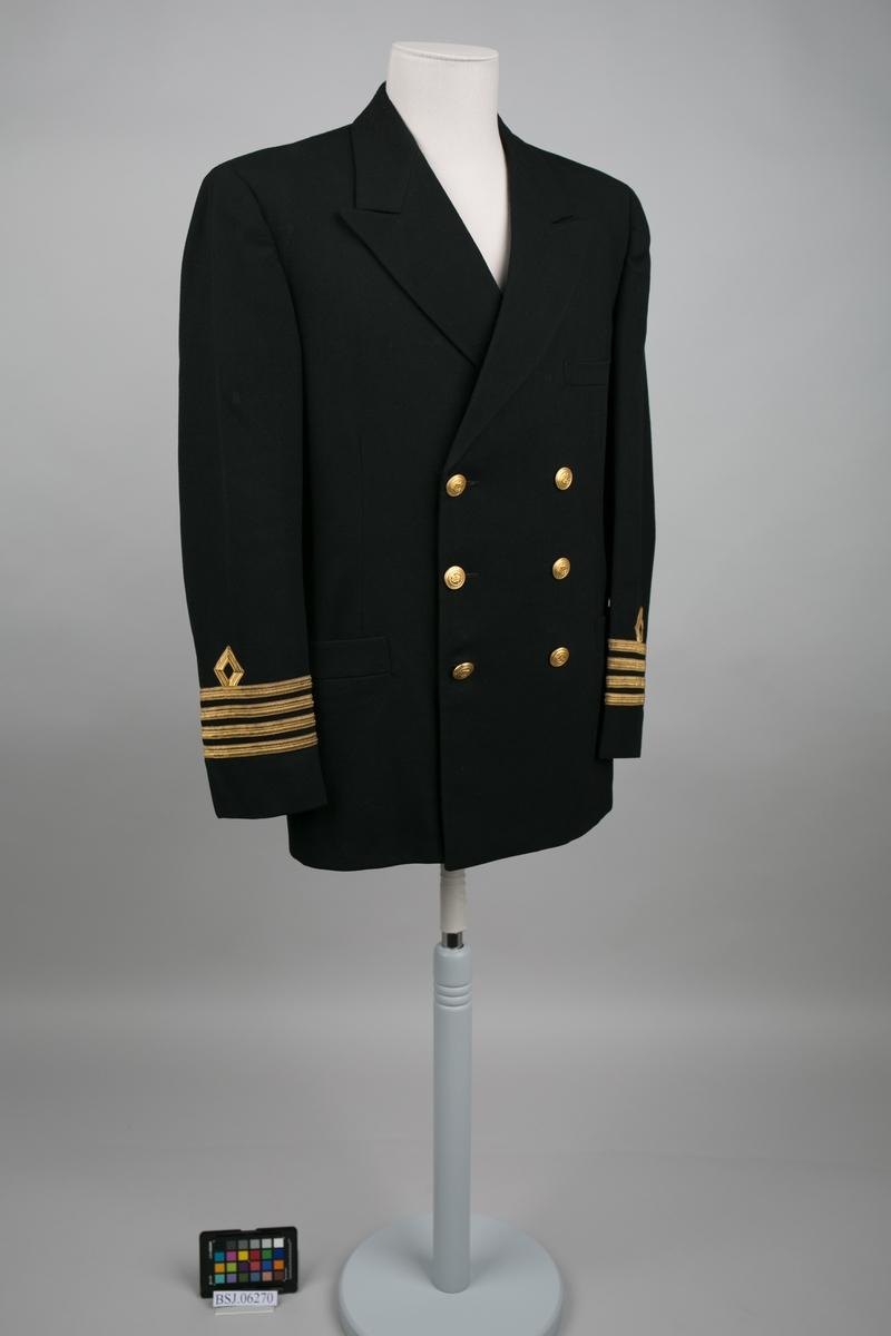 Kaptein uniformjakke med 4 stk. gullbånd og distinksjoner på erme. Dobbelspent med til sammen 8 stk. knapper i gullfarge med motiv av anker.