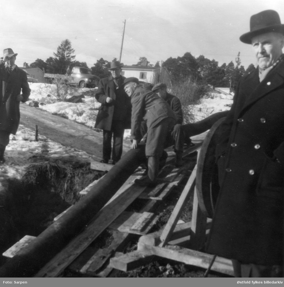 Vannledning legges til Opsund i Sarpsborg, ca. 1958? Ingeniør Engelsen, ant. mann til høyre.