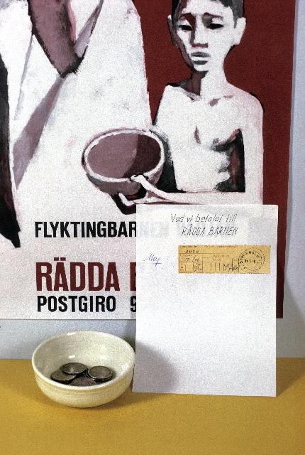 """Seriebild M 40b. Affisch, vid postkassa på postkontoret Solna 1, på vilken Flyktingbarnen vädjar om bidrag till Rädda Barnens postgiro 900 100. Vid sidan om ett anslag med handskriven text: """"Vad vi betalat till Rädda Barnen"""" """"Maj"""" och ett postgirokvitto med beloppet 47 kr 60 öre, stämplat """"Stockholm 12 31.5.1963"""". En liten porslinsskål med några mynt står intill."""